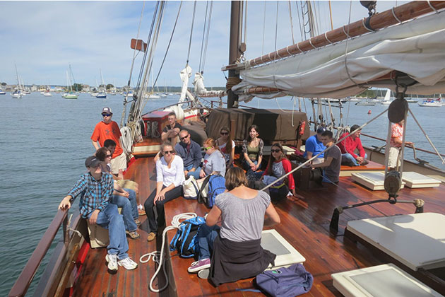 Helen Rozwadowski, associate professor of history and maritime studies (wearing a gray shirt), wraps up the class by reviewing the reading for the day and discussing how it relates to the day's work aboard the Whaler. (Nathaniel Trumbull/UConn Photo)