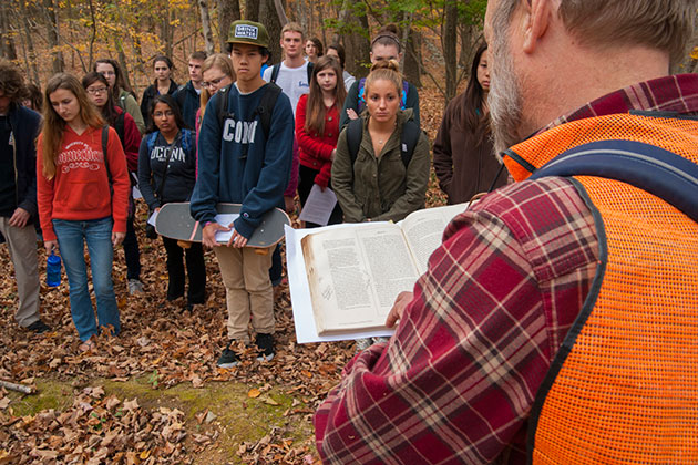 Robert Thorson reads passages of Thomas Cole and Henry David Thoreau to a group of students during a field trip, part of an honors course on Walden and the American Landscape. (Sean Flynn/UConn Photo)