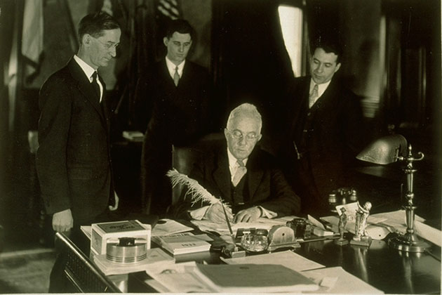Gov. Wilbur Cross, center, signs the bill that made Connecticut Agricultural College the Connecticut State College in 1933. Standing, from left, are President Charles McCracken, the school's sixth president; John Robinson '33, who led the name change; and James Gwinn '31, leader of alumni. (Photo courtesy of University of Connecticut Libraries, Archives & Special Collections)