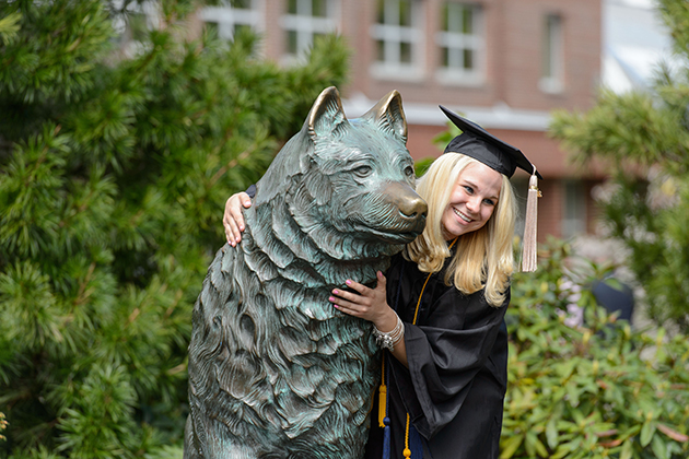 Chelsea McCallum of Somers poses for a photo with the Jonathan statue after graduating with a bachelor's degree in business in 2013. (Peter Morenus/UConn Photo)