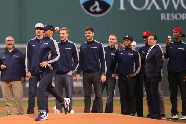 Basketball standout Shabazz Napier '14 (CLAS) throws out the first pitch at Fenway Park in Boston April 22, watched by Gov. Dannel P. Malloy, second from right, and members of the UConn men's team.