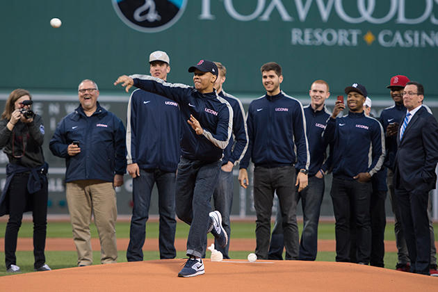 Basketball standout Shabazz Napier '14 (CLAS) throws out the first pitch at Fenway Park in Boston on April 22, watched by Gov. Dannel P. Malloy, far right, and members of the Huskies men's basketball team. The NCAA National Championship UConn team was honored in a pre-game ceremony, before the Red Sox vs. Yankees game. (Boston Red Sox Photo)