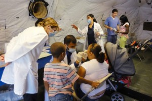 Urban Service Track alumna, Dr. Jennifer Jaskolka (standing far left), observes current UST scholar and third-year dental student, Himank Gupta, performing a dental exam during a free health clinic. (Photo provided by Petra Clark-Dufner)