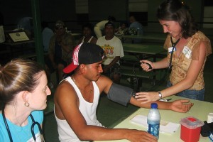 UST alumna, Kara O'Brien (standing), doing a blood pressure check during a free health clinic. (Photo provided by Petra Clark-Dufner)