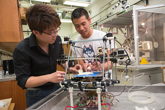 Senior chemical engineering student Derek Chhiv, right, discusses with Professor Anson Ma his group's prototype for an artificial kidney. The prototype was generated through 3-D printing. (Al Ferreira for UConn)