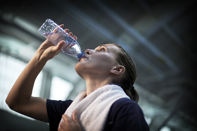 An athlete rehydrates after exercising. (Paul Horton for UConn)