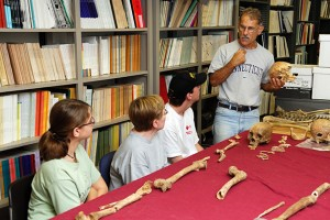 Bellantoni discusses skeletal remains with students at an archaeology field school session.