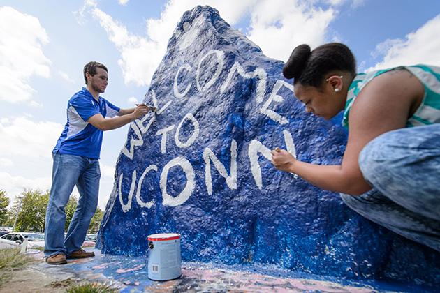 Drew Vandemore '15 (CAHNR), left, and Jasmine Kirkland '16 (CAHNR) paint 'Welcome to UConn' on the rock near the UConn Foundation Building on Aug. 20, 2014. (Peter Morenus/UConn Photo)