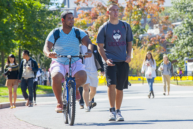 Groups of students walk across campus, including a student on a bike. (Sean Flynn/UConn Photo)