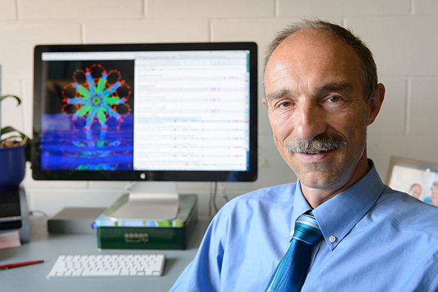 Peter Burkhard, professor of molecular and cell biology, with a computer image of the protein nanoparticle he designed. (Peter Morenus/UConn Photo)
