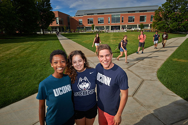 Students wearing UConn apparel pose for photos on the Student Union Mall. (Peter Morenus/UConn Photo)