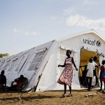 Children displaced by fighting in South Sudan stand outside a tented school run by UNICEF. (UNICEF Photo)