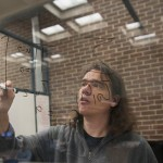 Ralf Schiffler, associate professor of math, ponders an equation. (Sean Flynn/UConn Photo)