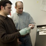 David Goldhamer, professor of molecular and cell biology, center, and doctoral student Michael Wosczyna examine a tissue sample in their lab. (Dan Buttrey/UConn File Photo)