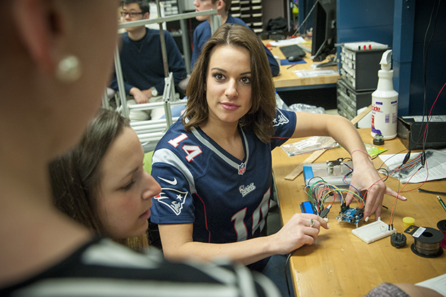 Alyssa Merkle '15 (ENG), Patriots cheerleader, works on her senior project in engineering. (Sean Flynn/UConn Photo)