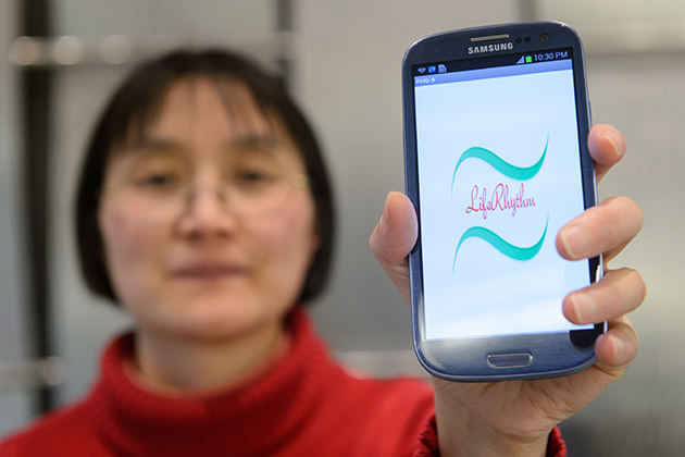 Bing Wang, associate professor of computer science and engineering, holds a smartphone with an application created to help screen for depression. (Peter Morenus/UConn Photo)