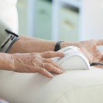 An elderly woman monitoring her blood pressure at home. (iStock Photo)