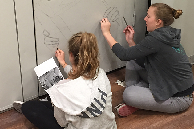 Two students from Cora Lynn Deibler's class use graphite pencil to get a better image on the wall before painting. (Cora Lynn Deibler/UConn Photo)