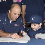 Baseball Head Coach Jim Penders shows five-year-old Grayson Hand where to sign his National Letter of Intent. (Stephen Slade '89 (SFA) for UConn)