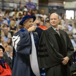 University Marshall Michael Darre hoods Philip Lodewick '66 (BUS), '67 MBA, as he receives an honorary degree at the School of Business commencement ceremony at Gampel Pavilion on May 11, 2014. (Peter Morenus/UConn File Photo)