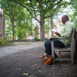History professor Jelani Cobb, director of the Africana Studies Institute, reading a book in the Benton Museum courtyard. (Sean Flynn/UConn Photo)