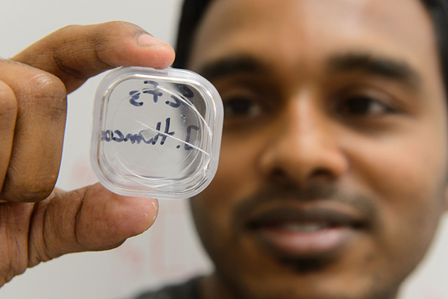Sahan Handunkanda, a graduate student in physics, holds up a crystal of scandium trifluoride. (Peter Morenus/UConn Photo)