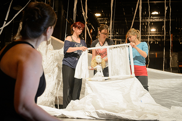 Margarita Blush, assistant professor of performance, left, looks on as Ceili Clemens '01 (SFA), Sarah Nolen '15 MFA, and Lucia Rich, a professional performer, operate the puppet 'Aya' during a rehearsal for 'Unfolding the Story: A Journey of Her Own.' (Peter Morenus/UConn Photo)