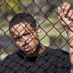 A teen looks out from behind a fence. (iStock Photo)