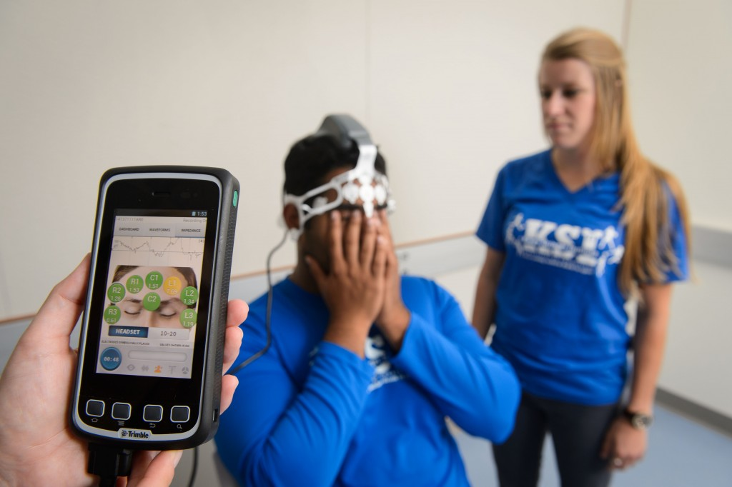 A device to evaluate concussions is demonstrated by Rohin Thomas '17 (CAHNR), left, and Sarah Attanasio '16 (CAHNR). (Peter Morenus/UConn Photo)