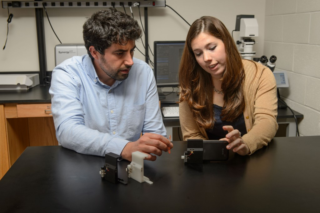 Graduate student Stephanie Knowlton, right, and Savas Tasoglu, assistant professor of mechanical engineering, with a device to analyze blood for sickle cell disease. (Peter Morenus/UConn Photo)