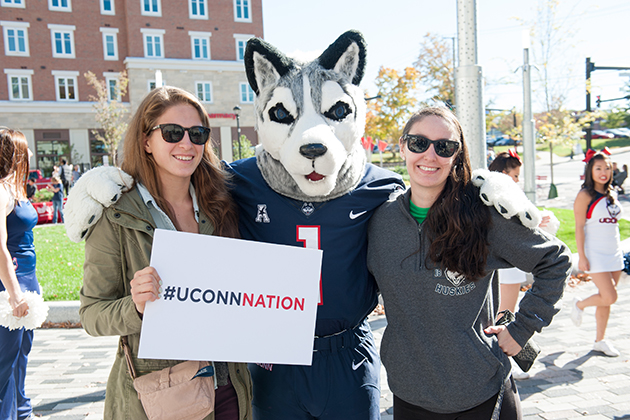 Jonathan the Husky mascot poses with fellow members of UConn Nation at Storrs Center during Huskies Forever Weekend. (Roger Castonguay for UConn)