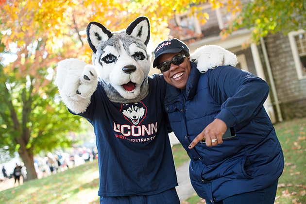 Monique Cotton Kelly, executive director of UConn Alumni, poses with Jonathan the Husky mascot during Huskies Forever Weekend on Oct. 11, 2015. (Roger Castonguay for UConn)