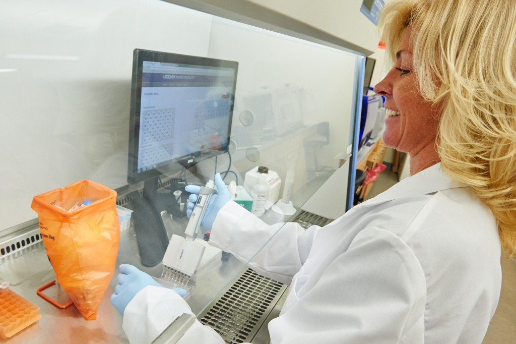 Susan Janton, research assistant in molecular and cell biology, uses a micropipette at the Microbial Analysis, Resources and Services lab. (Peter Morenus/UConn Photo)
