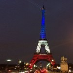 The Eiffel Tower in Paris, lit up in red, white, and blue.