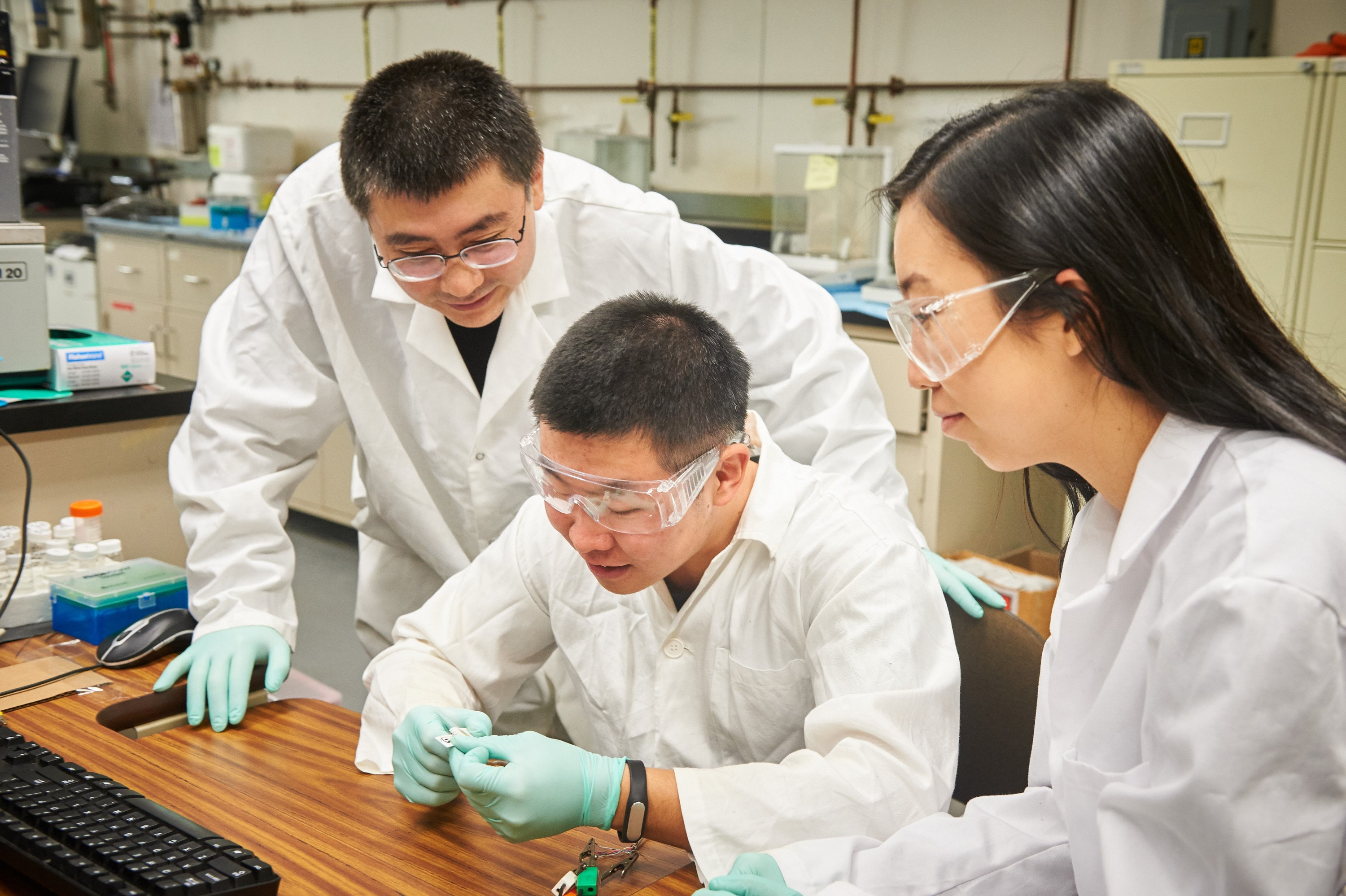 Yu Lei, associate professor of chemical & biomolecular engineering, left, and graduate students Qiuchen Dong and Xiaoyu Ma connect a toxic chemical sensor to a cable in a lab at the United Technologies Engineering Building on Feb. 2, 2016. (Peter Morenus/UConn Photo)