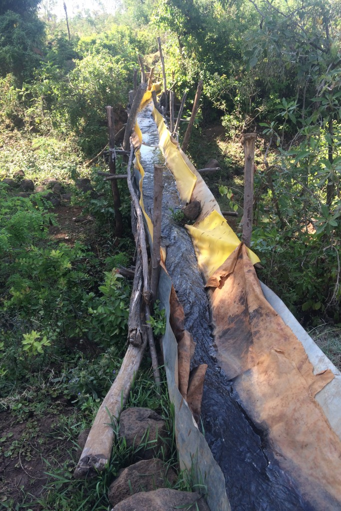 A makeshift aqueduct, constructed by the villagers using plastic tarps, sheet metal and sticks. The inventive structure has a large hole in the underside, which results in substantial water loss.
