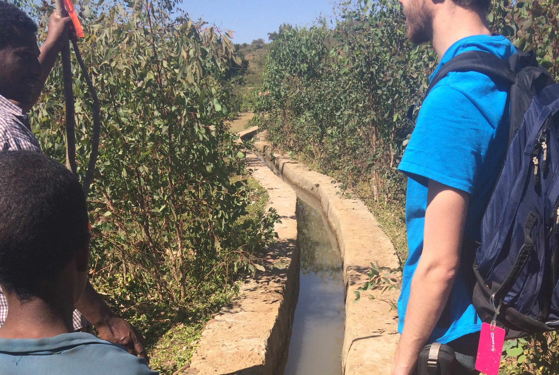Ryan Cordier '18 (ENG), right, views the current irrigation system in an Ethiopian village along with two local residents.