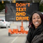 Marisa Auguste with a traffic safety sign on April 8, 2016. (Peter Morenus/UConn Photo)