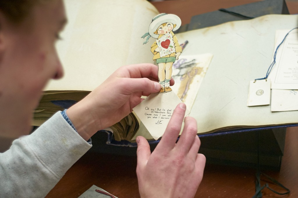 Charles Smart '18 (CLAS) reviews a scrapbook from the early 1920s kept by Flora Howe '25 at the University Archives on April 6, 2016. (Peter Morenus/UConn Photo)