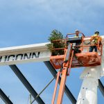Workers uncover a decorated beam and place an evergreen tree during the topping off ceremony of the Innovation Partnership Building on May 31, 2016. (Peter Morenus/UConn Photo)