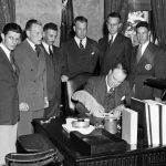 Gov. Raymond Baldwin, center, signs the bill establishing Connecticut State College as The University of Connecticut on May 26, 1939. Looking on are, left to right: Normand P. DuBeau of Willimantic, editor-in-chief of The Connecticut Campus; William Crowley of New Britain, president of the Student Senate; Andre Schenker, professor of history; President Albert N. Jorgensen; George Pinckney, alumni secretary; and Edward Finn of Hartford, a student. (Photo courtesy of University Archives)