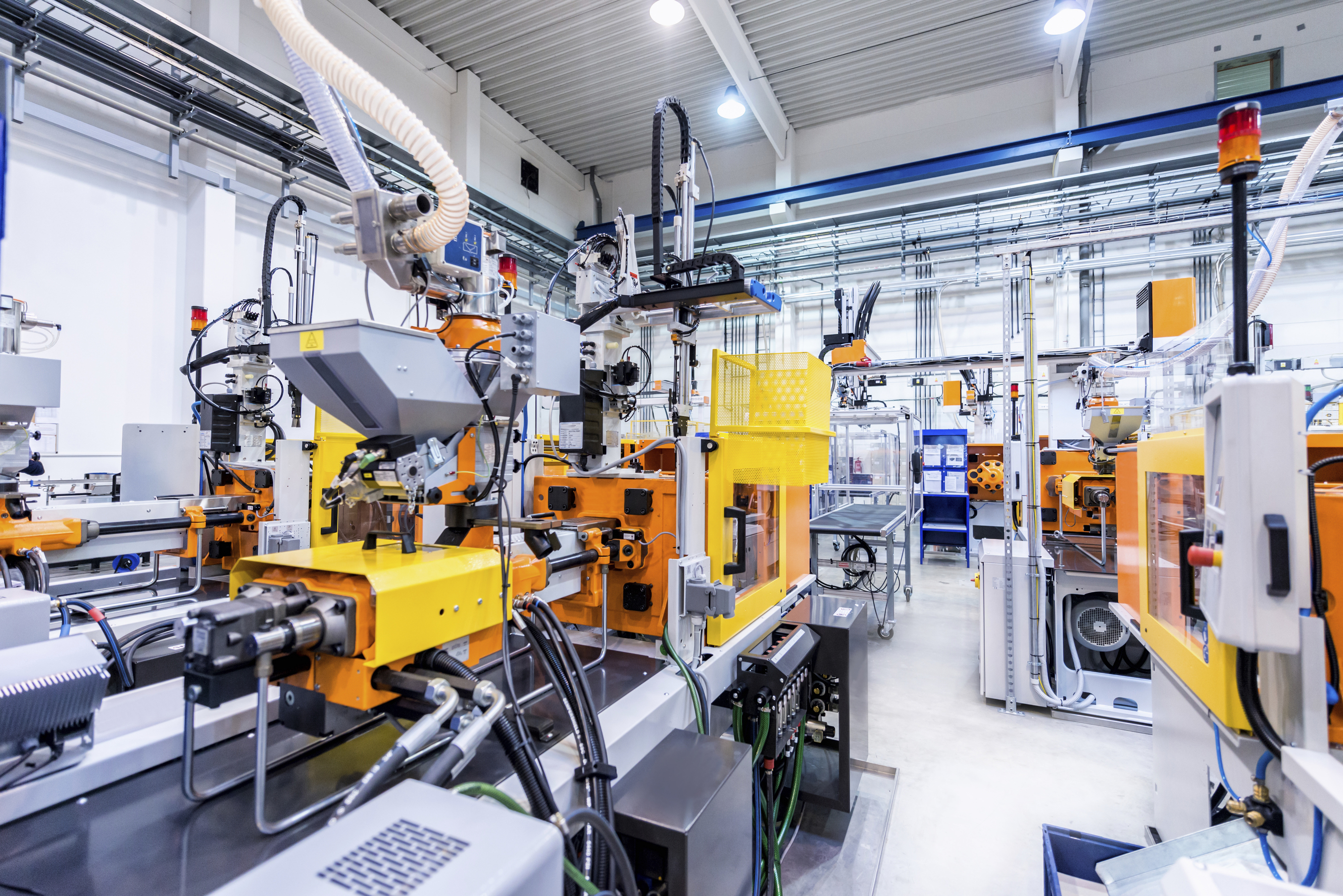 Horizontal color image of large group of automated injection moulding machines for plastic parts production. (iStock Photo)