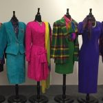 From left, long, color-blocked five-button blazer with gold, purple, and black pieced rayon crepe; matching black and purple skirt by Nichole Miller, 1987; turquoise suede power suit with long '80s lapels, with polyester jacquard blouse with jewel-toned paisley overprint by Hastings and Smith, 1985; fuchsia silk jacquard dress by Arnold Scaasi, 1988; green and yellow plaid skirt suit, with pink red and purple mohair, with matching Kelly green tweed skirt by Mary Ann Restivo, 1982; deep violet crepe de chine sheath gown by Maggy of London, 1983;