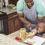 An African American father makes a peanut butter sandwich for his 5 year-old son's lunch. (iStock Photo)