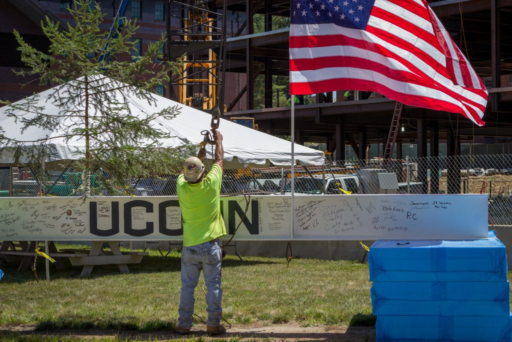 A construction worker prepares the final beam for hoisting.