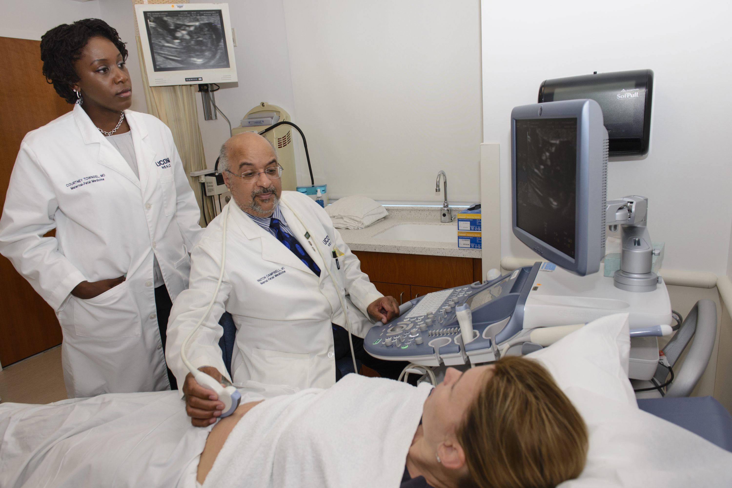 Dr. Courtney Townsel, left, looks on as Dr. Winston Campbell performs an ultrasound on an expectant mother. (Janine Gelineau/UConn Health Photo)