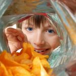 Child looking at chips in a bag. (iStock Photo)