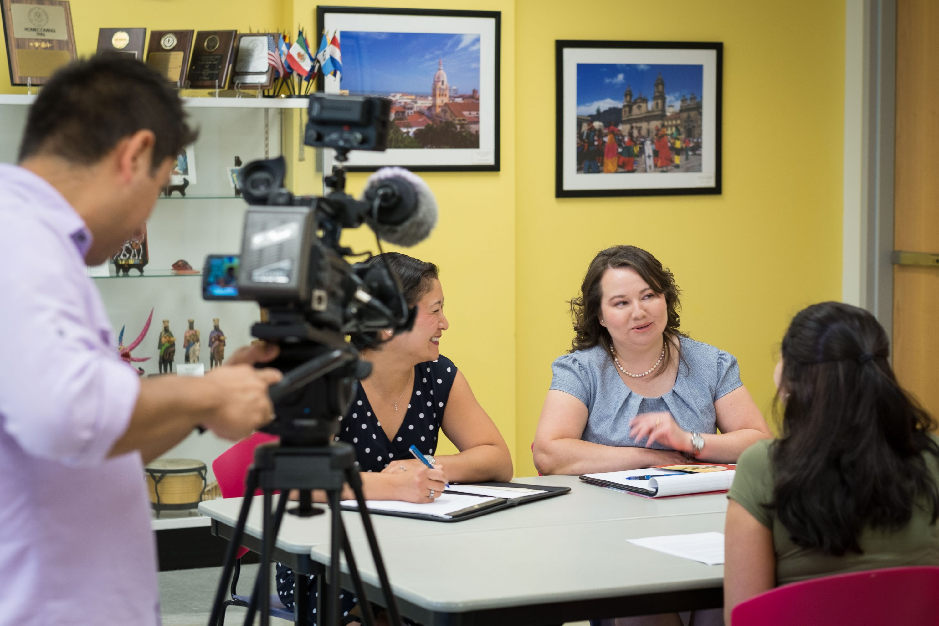 Juan Carlos Sanchez of Univision , left, records Jen Morenus '97 (SFA), assistant director, Fany D. Hannon '08 MA, director, and Natalia Gutierrez '18 (ENG) at the Puerto Rican/Latin American Cultural Center on Aug. 12, 2016. (Peter Morenus/UConn Photo)