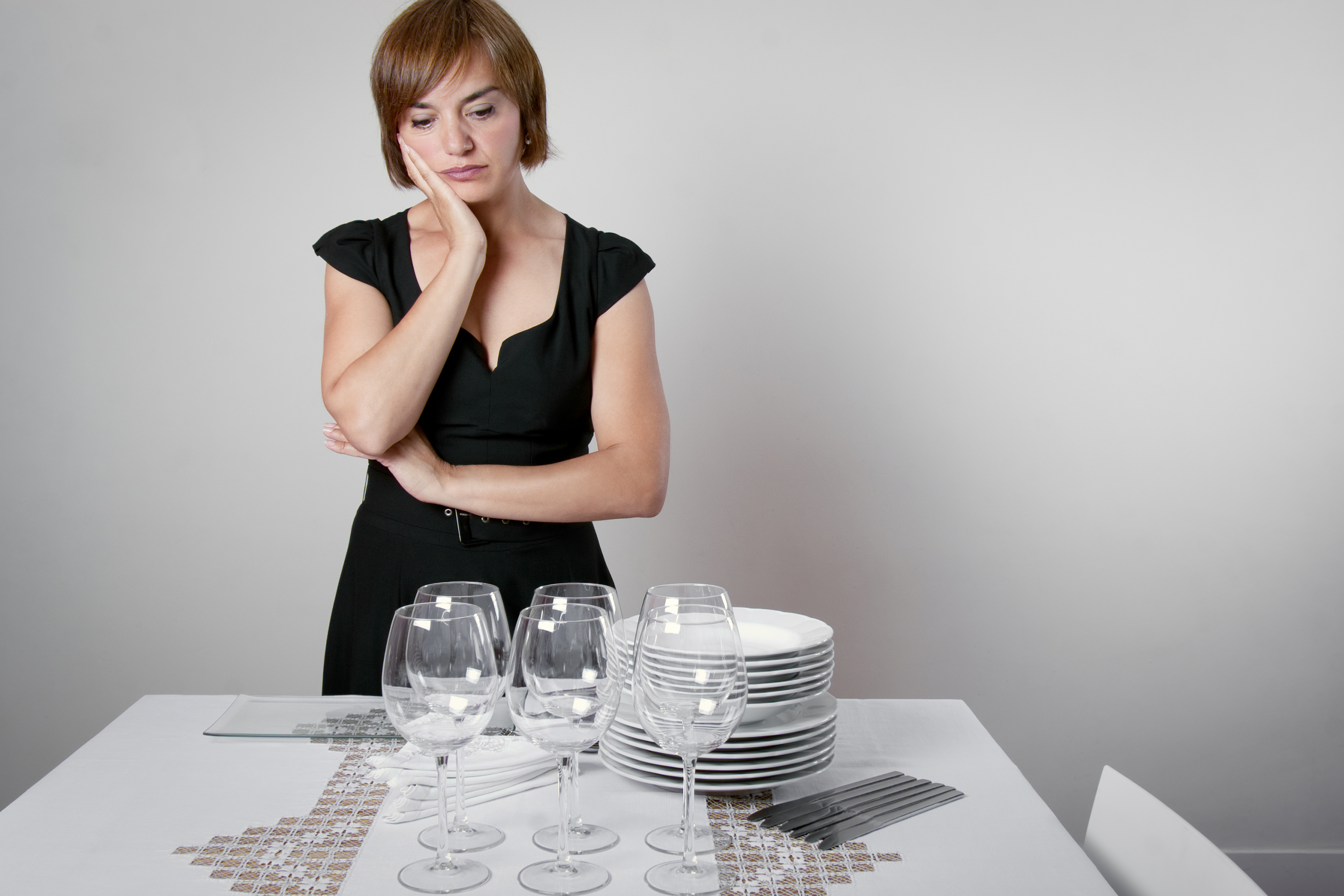 Worried woman setting the table for a celebration. (ASIFE, Getty Images)