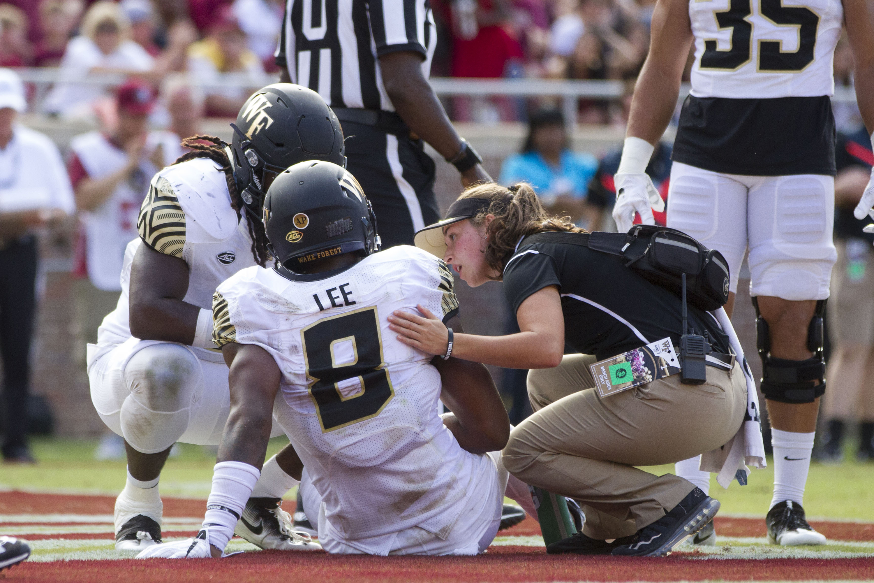 An athletic trainer attends to an injured football player. (Photo by Logan Stanford/Icon Sportswire via Getty Images)